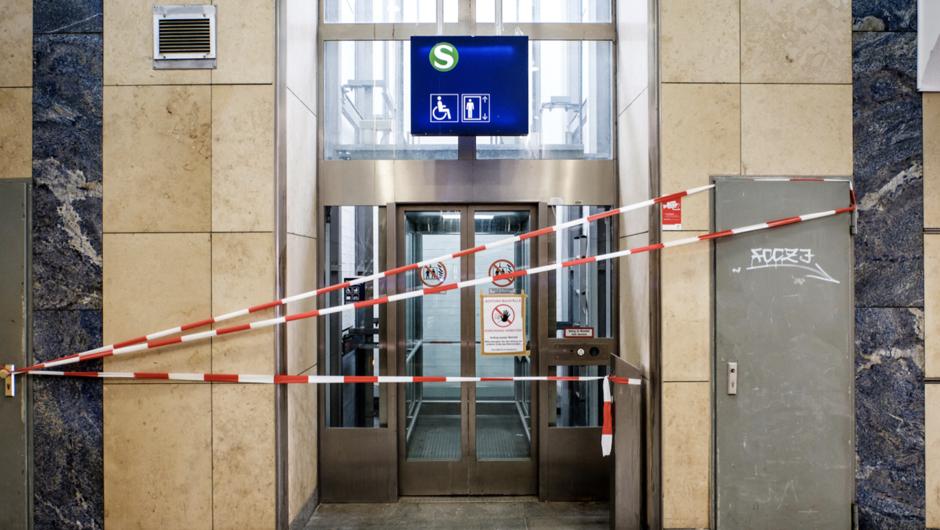 Red-white barrier tape blocks the entrance to a broken elevator. Seen at a German S-Bahn railway station.