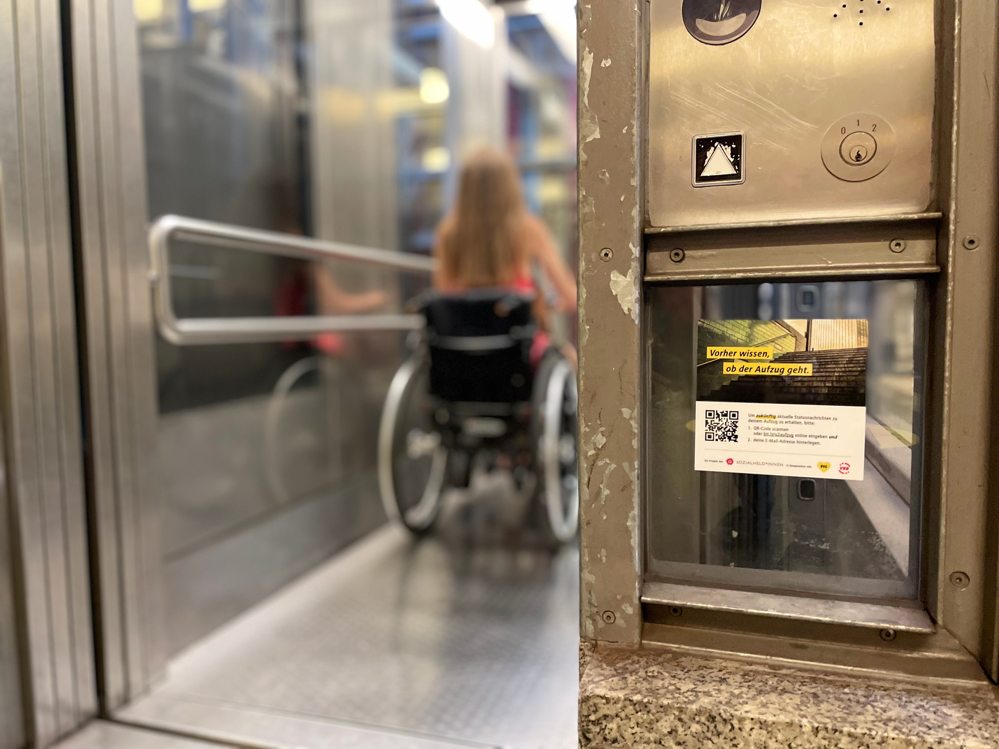 A person using a wheelchair right after entering an elevator. Right under the elevator's controls, a sticker with a QR code advertises that you can get notifications from this elevator if there is a service disruption.